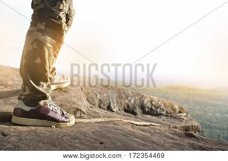 Close up of man standing on top of a mountain. Sucessful struggle concept.