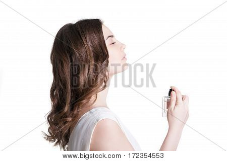 young woman spraying the perfume on her neck
