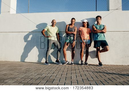 Multiracial Friends Posing Outdoors By A Wall