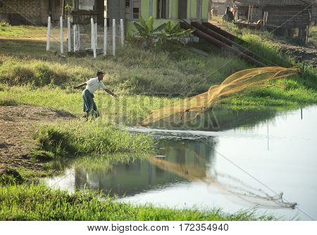 Silhouette of a fisherman throwing a fishnet in a lake. February 22 2014 - Yangon Myanmar