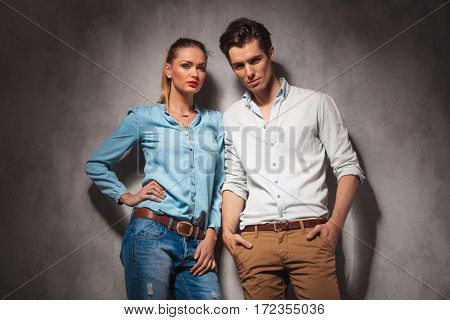 beautiful casual couple standing together in studio and look at the camera