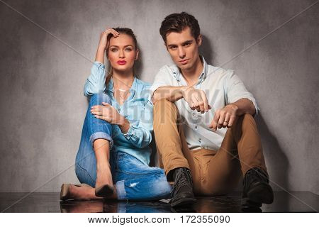 young casual couple resting on the floor and both look at the camera in studio