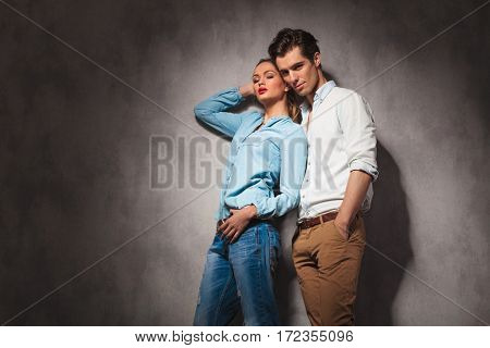 sexy casual woman leaning her back on boyfriend and poses for the camera in studio