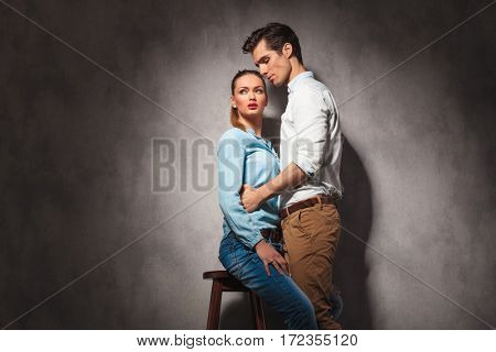 man holding his seated casual girlfriend , studio picture