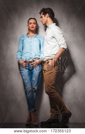 full body picture of a young casual couple standing together in studio