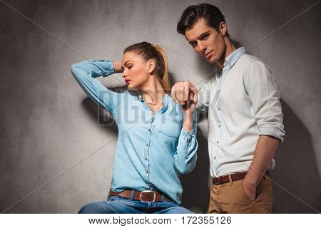 young couple holding hands while woman is sitting and man standing in studio