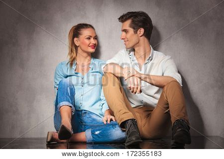 young casual seated couple laughing at each other while resting in studio