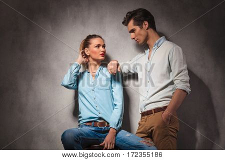 young casual couple looking at each other, woman is sitting on a stool and man is standing with elbow on her shoulder