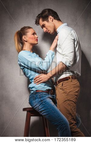 in love couple , woman sitting and man standing and look at eachother in studio