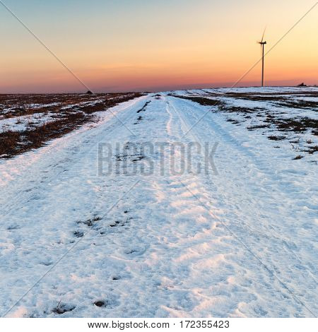 Wintry Field in Snow with Single Wind Turbine in Background