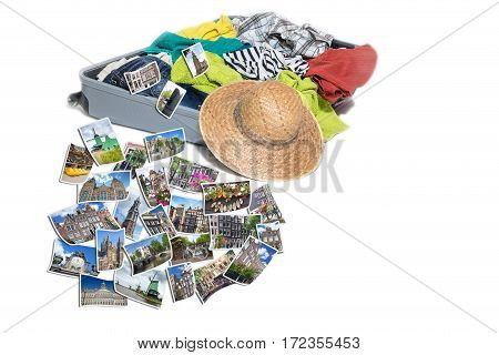 Studio shot of a suitcase with scattered clothing and straw hat. Photos of Amsterdam and Netherlands landmarks are lying in front of the suitcase. Everything is on a white background.