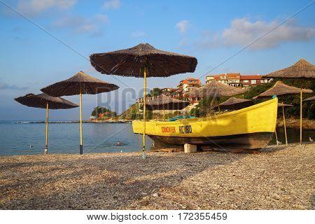 Nesebar Bulgaria - September 05 2014: Straw beach umbrellas and rescue boat on a pebble beach. Seaside resort and ancient old town Nesebar in Bulgaria. Bulgarian Black Sea Coast.