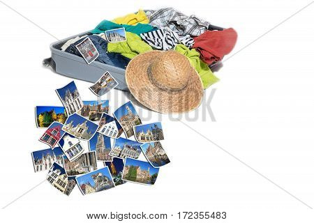 Studio shot of a suitcase with scattered clothing and straw hat. Photos of Bruges landmarks are lying in front of the suitcase. Everything is on a white background.