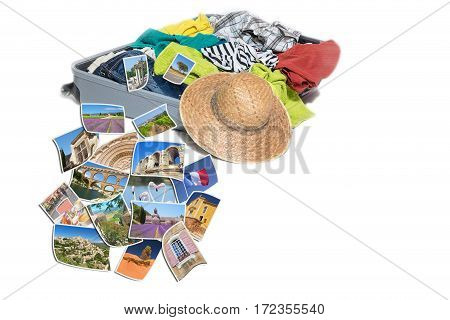 Studio shot of a suitcase with scattered clothing and straw hat. Photos of Provence landmarks are lying in front of the suitcase. Everything is on a white background.