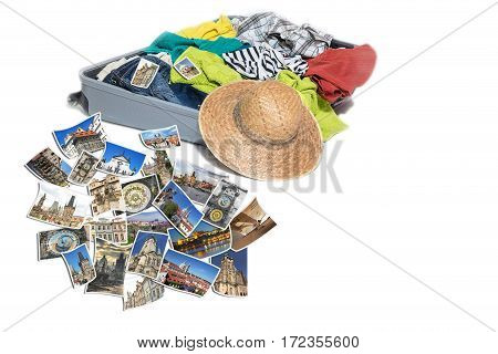 Studio shot of a suitcase with scattered clothing and straw hat. Photos of Prague (Czech Republic) landmarks are lying in front of the suitcase. Everything is on a white background.
