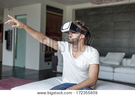 Young man with VR glasses playing virtual reality