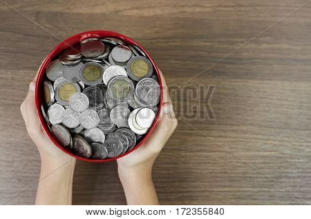 Top view Money in the red bucket on wooden table background Kid hands holding a money bucket.