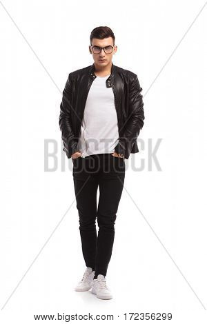 young man in leather jacket and jeans walking on white studio background