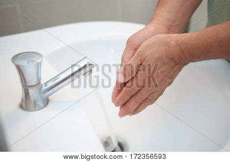 Close up Washing and cleaning of hands under running water Old people hands.