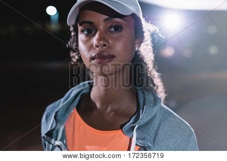 Close up shot of fitness woman in city at night. Beautiful female runner looking away.