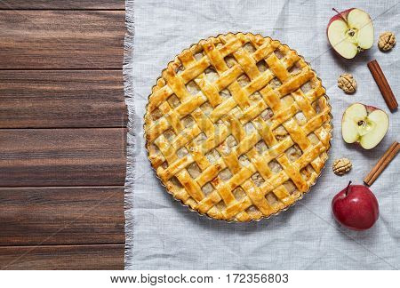 Homemade rustic apple pie preparation greased with egg yolk on dark wooden table. Traditional dessert for Independence Day in America. Flat lay. Copy space.