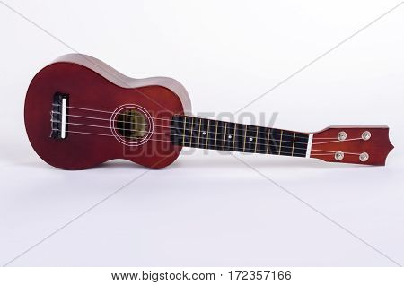 Modern Hawaiian guitar with four strings on a white background isolated