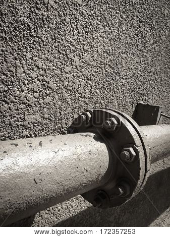Old steel or metal pipes with bolts on rough wall background.