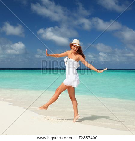Fashion woman dancing on the beach. Happy island lifestyle. White sand, blue cloudy sky and crystal sea of tropical beach. Vacation at Paradise. Ocean beach relax, travel to Maldives islands