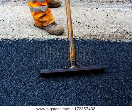 Worker on Asphalting paver machine during Road street repairing works