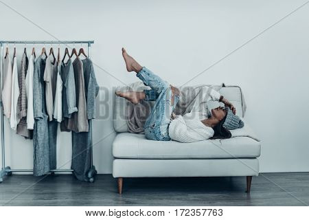 Lazy mood. Thoughtful young woman in casual wear touching her head with hand and putting feet up while lying on sofa at home near her clothes hanging on the racks