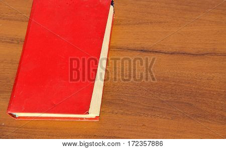 Old red book on the wooden table
