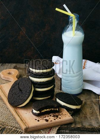 Homemade Chocolate Cookies With White Marshmallow Cream And Botle Of Milk On Dark Background. Select