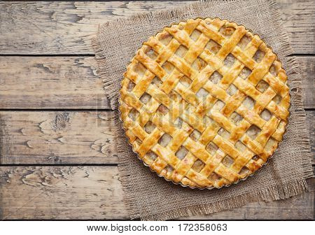 Apple pie tart with raisins, nuts and cinnamon on vintage wooden background texture. Traditional dessert for Independence Day in America. Rustic style. Top view