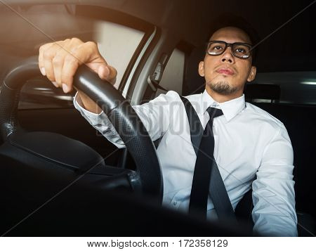 Close up Asian businessman driving a car.