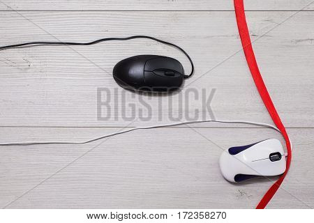 Interactive race on speed between white and black computer mouse on wooden background. Input device for cursor control. Red ribbon. Competition in the business red tape.