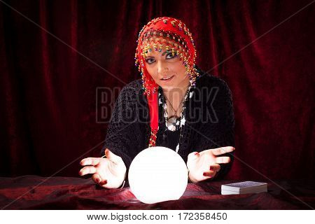 Studio shot of crazy fortune teller with crystal ball