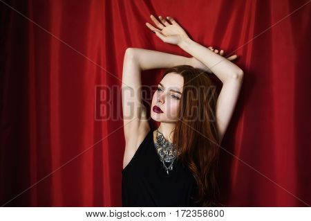Beautiful red-haired girl in black dress with red lips on red background looking away. Fashion photography. Bright appearance. Red hair. Keep hands over head