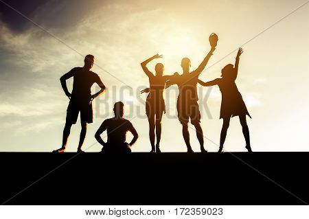 Silhouettes of five people posing on sunset backdrop. Friends or friendship concept