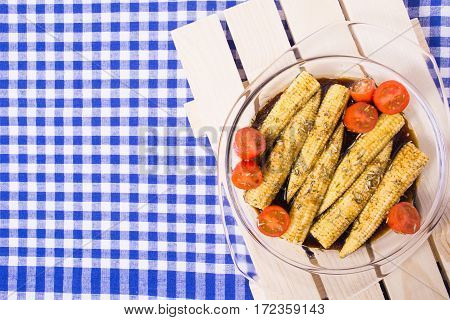 Baby corn and tomatoes with soy marinade of soy sauce rosemary olive oil and garlic on the blue tissue