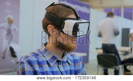 Virtual reality game. Young man using virtual reality glasses. VR