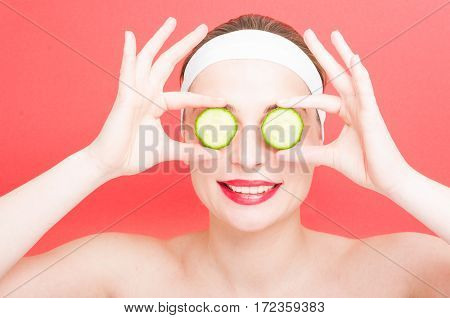 Young Female Holding Slices Of Cucumber On Eyes