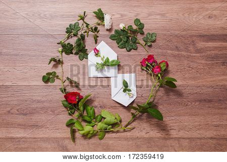 Open envelopes frame of red and white roses and red hearts on wooden background. Greeting card. Conceptual photography. Wedding invitation card. Valentine day. Flat lay top view copyspace mock up