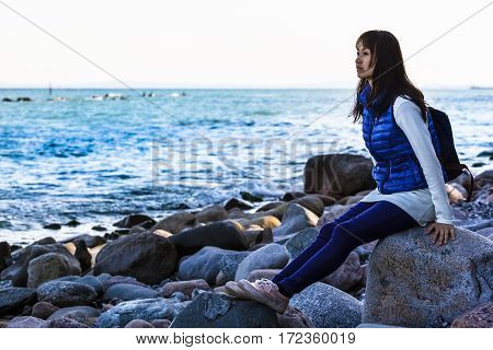 Young woman resting from hiking activity, sitting at stone beach and view to the blue sea (copy space)