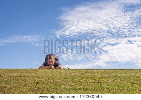 Happy caucasian man in casual style with backpack lying down on green field. Blue sky with white clouds on background.