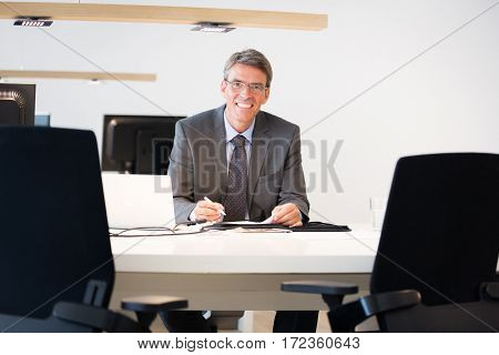 a financial advisor sitting at his desk, ready to help you with your investments.