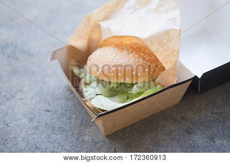 Fresh hamburger on a bun in a carton box
