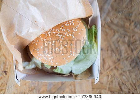 Delicious cheeseburger in cardboard box on wooden background
