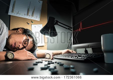 Asian man wear eyeglasses be ill and having heart attack. Pills spilling out of pill bottle foreground. Feeling tired exhausted unconscious overworked. Asian designer wear eyeglasses fall asleep.