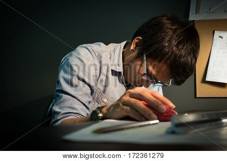 Feeling tired. Creative editor holding mouse of computer while sleeping on office desk. Asian creative editor wear eyeglasses fall asleep.