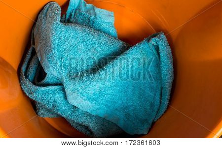 The Old blue towel In dirty orange plastic basin